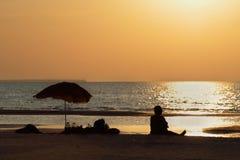 Kvinnasilhouette på solnedgången Arkivbild