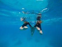 Kvinnasimning i blått vatten Härlig kvinna under vatten för dyk till korallreven arkivbild