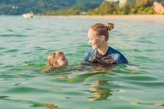 Kvinnasimninginstruktören för barn undervisar en lycklig pojke att simma i havet royaltyfria bilder