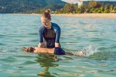 Kvinnasimninginstruktören för barn undervisar en lycklig pojke att simma i havet royaltyfri foto