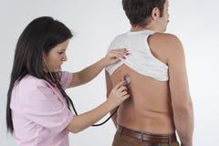 Kvinnasjuksköterska Auscultation en man fotografering för bildbyråer