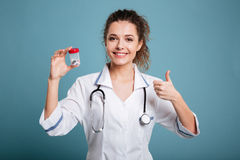 Kvinnasjuksköterska i preventivpillerar för labblagvisning och tumme som isoleras upp royaltyfria bilder