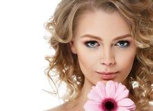 Kvinnaskönhetstående med blomman i lockigt blont hår för hår som isoleras på vit arkivbilder