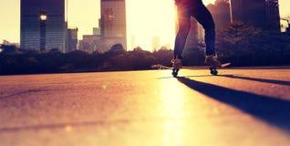 Kvinnaskateboarder som skateboarding på soluppgångstaden arkivbild