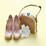 Kvinnaskor med handväskan och blomman Arkivbild