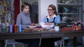 Kvinnaskräddare med klienten som väljer torkduken i atelier lager videofilmer