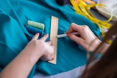 Kvinnaskräddare som arbetar på en klädsömnad som syr mäta fa Fotografering för Bildbyråer