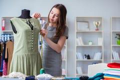 Kvinnaskräddare som arbetar på en klädsömnad som syr mäta fa Arkivfoto