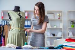 Kvinnaskräddare som arbetar på en klädsömnad som syr mäta fa Arkivbilder