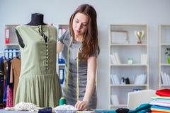 Kvinnaskräddare som arbetar på en klädsömnad som syr mäta fa Arkivfoton