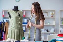 Kvinnaskräddare som arbetar på en klädsömnad som syr mäta fa Arkivbild