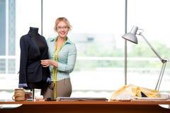Kvinnaskräddaren som arbetar på nya kläder Royaltyfri Fotografi