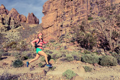 Kvinnaslingaspring i berg med ryggsäcken Royaltyfri Bild
