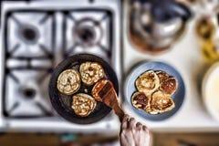 Kvinnasmåfiskpannkakor i en stekpanna på en gammal gasugn Begrepp: Matlagning som bakar ovanför sikt Fritt avstånd för text royaltyfri foto
