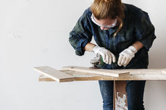 Kvinnasnickaren som använder att skjuta för hammare, spikar på ett trä Arkivbilder