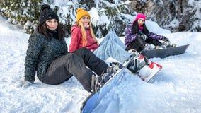 Kvinnasnowboarders som sitter på snön Royaltyfria Bilder