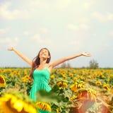 Kvinnasommarflicka som är lycklig i solrosblommafält Arkivbild