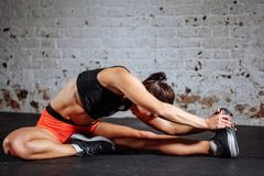 Kvinnasport som sträcker i idrottshall med mats för tegelstenvägg och svart Arkivbild