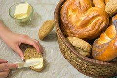 Kvinnaspridning smöret på skivan av bröd och olikt bröd i korgen Royaltyfria Bilder
