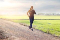 Kvinnaspringövning på den lantliga vägen av grön fältsolnedgångbaksida Royaltyfria Bilder