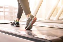 Kvinnaspring i en idrottshall på ett trampkvarnbegrepp för att öva, kondition och sund livsstil arkivbild