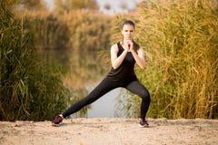 Kvinnaspring i kvinnan för sund lifestyleYoung för höstnedgångskog som den sportive gör övningar i höst Idrottskvinnasträckning arkivbilder