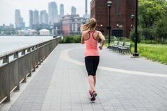 Kvinnaspring i New York City parkerar bärande sportkläder royaltyfri foto