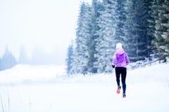 Kvinnaspring i vinter, konditioninspiration och motivation arkivbilder