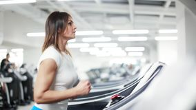 Kvinnaspring på den endast trampkvarnen i idrottshallen lager videofilmer