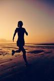 Kvinnaspring på soluppgångstranden Royaltyfri Fotografi
