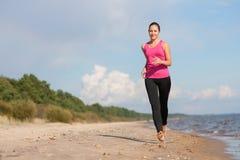 Kvinnaspring på stranden Royaltyfria Bilder