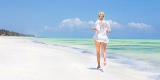 Kvinnaspring på stranden i den vita skjortan Royaltyfria Bilder