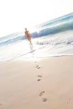 Kvinnaspring på stranden i solnedgång Arkivbilder