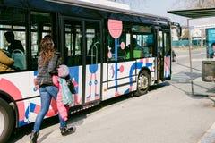 Kvinnaspring som fångar bussen Arkivbild
