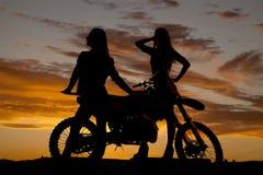 Kvinnaställning för kontur två med motorcykeln royaltyfri foto