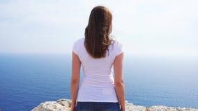 Kvinnaställning på kanten av klippan på solig dag i ultrarapid Bekymmerslös kvinnlig blick på sikten av det blåa havet arkivfilmer