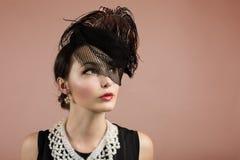 Kvinnastående i Retro svart hatt med en skyla Arkivbild