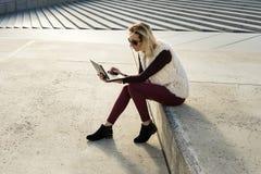 Kvinnastående i sommar Flickan sitter utanför ett kontor och ett innehav en minnestavla Kvinnlig med anteckningsboken Royaltyfria Foton