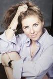 Kvinnastående i studio på en bakgrund av den gråa väggen Royaltyfri Fotografi