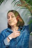 Kvinnastående med gröna sidor arkivfoto