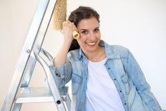 Kvinnastående med målninghjälpmedlet som är klart för hem- renovering Fotografering för Bildbyråer