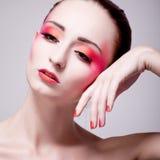 Kvinnastående med ytterlighetsmink i apelsin och rosa färg Royaltyfri Fotografi