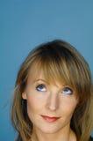 Kvinnastående på blått Arkivfoton