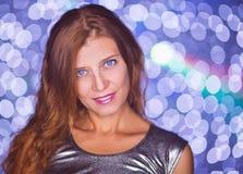 Kvinnastående på ljus bollbokehbakgrund royaltyfri fotografi