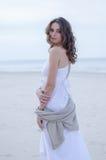 Kvinnastående på stranden Hellång lycklig härlig lockig-haired flicka, vinden som fladdrar hår Vårstående på stranden Royaltyfria Foton