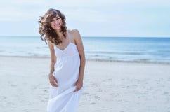 Kvinnastående på stranden Hellång lycklig härlig lockig-haired flicka, vinden som fladdrar hår Vårstående på stranden Royaltyfria Bilder