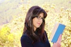 Kvinnastående som läser en bok royaltyfria bilder