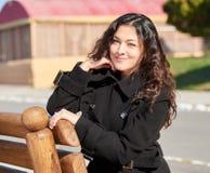 Kvinnaståenden i stad parkerar i nedgångsäsong royaltyfri bild