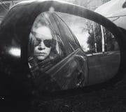 Kvinnastående i bilspegel Royaltyfri Bild