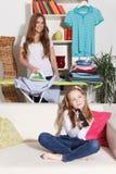 Kvinnastrykning, medan barnet håller ögonen på TV Arkivfoton